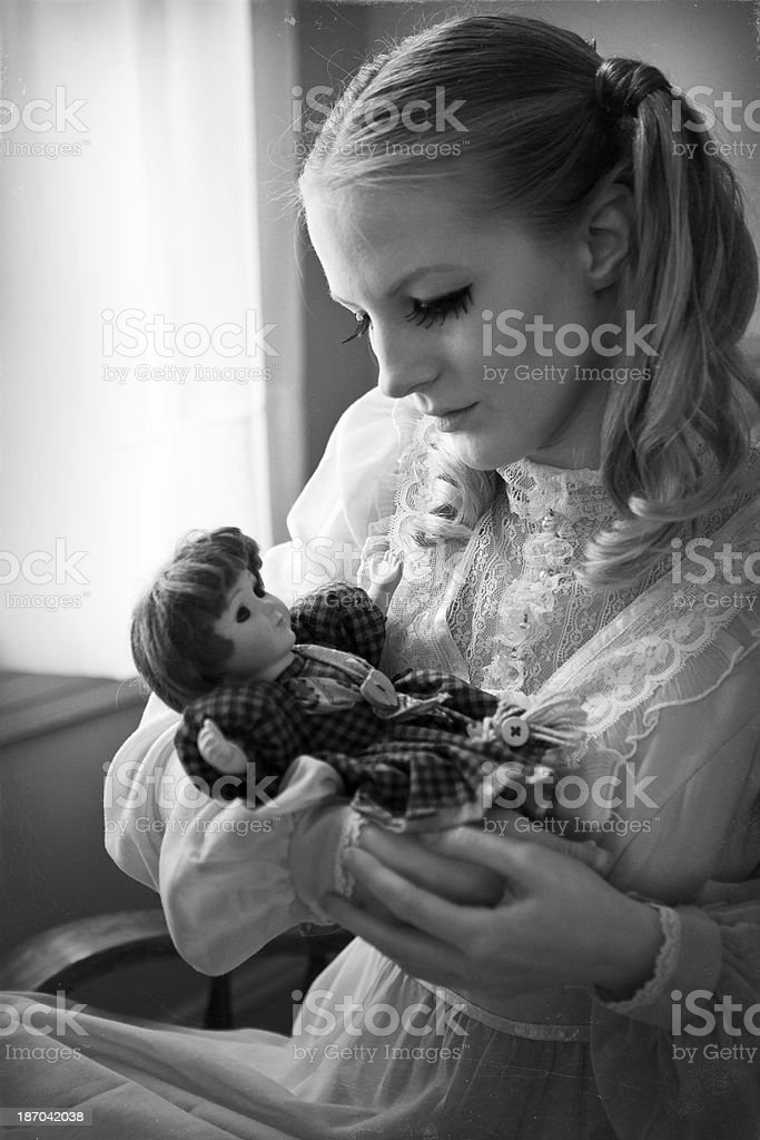 Old Fashioned Photo Of Girl Holding Baby Doll stock photo