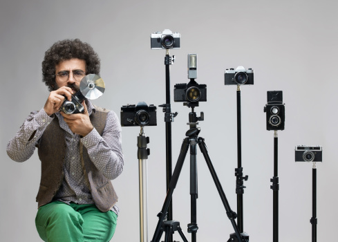 Portrait of old fashioned photographer with Analog SLR cameras