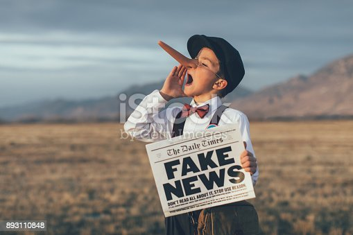 A news boy dressed in vintage knickers, newsboy hat and fake long Pinocchio nose stands with a fake newspaper in the middle of a field in Utah, USA. He is trying to sell you fake news.