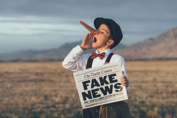 Old Fashioned Pinocchio News Boy Holding Fake Newspaper A news boy dressed in vintage knickers, newsboy hat and fake long Pinocchio nose stands with a fake newspaper in the middle of a field in Utah, USA. He is trying to sell you fake news. imitation stock pictures, royalty-free photos & images