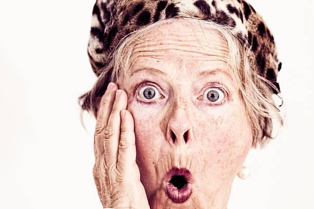 old fashioned senior woman fur hat surprise stock photo