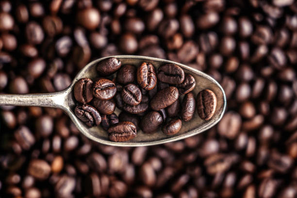 Old fashioned silver spoon with coffee beans over a background of roasted coffee beans stock photo