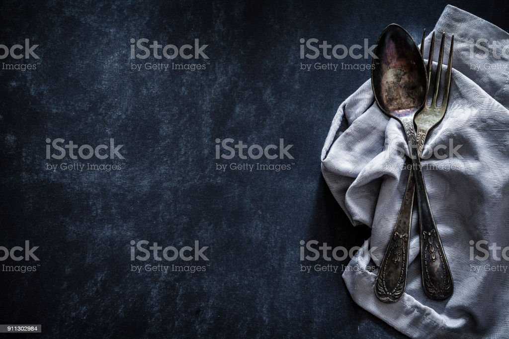 Old fashioned silverware shot from above on dark background stock photo