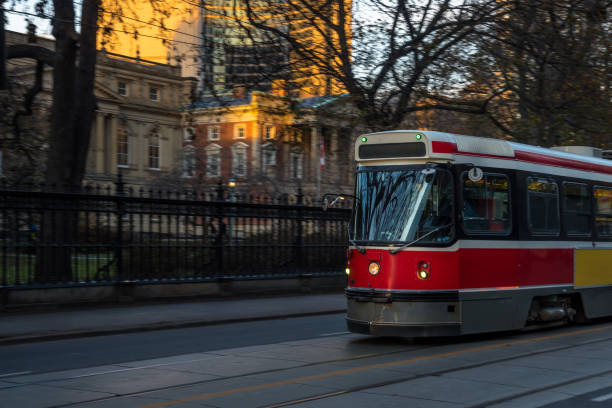 old fashioned streetcar in motion at sunset - toronto streetcar stock photos and pictures