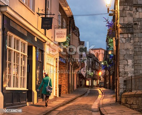 York, UK - A woman walking along The Shambles, a midieval street, and one of the best known historical streets in England.