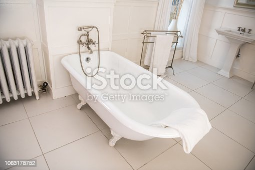 Old fashioned style bathroom with white bathtub