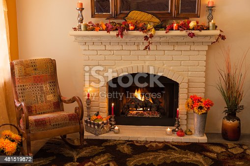 istock Old fashioned Thanksgiving fireplace and rocker in morning light 481519872