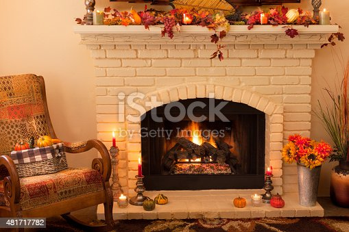 istock Old fashioned Thanksgiving fireplace and rocker in morning light -(P) 481717782