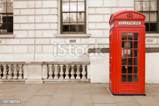Traditional old style UK red phone box isolated against a sepia tinted background.