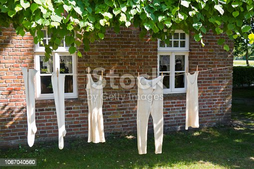 Old fashioned underwear is drying on a clothesline in the garden of an old farmhouse