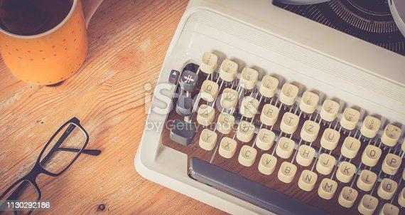 Vintage typewriter on a wooden desk, glasses