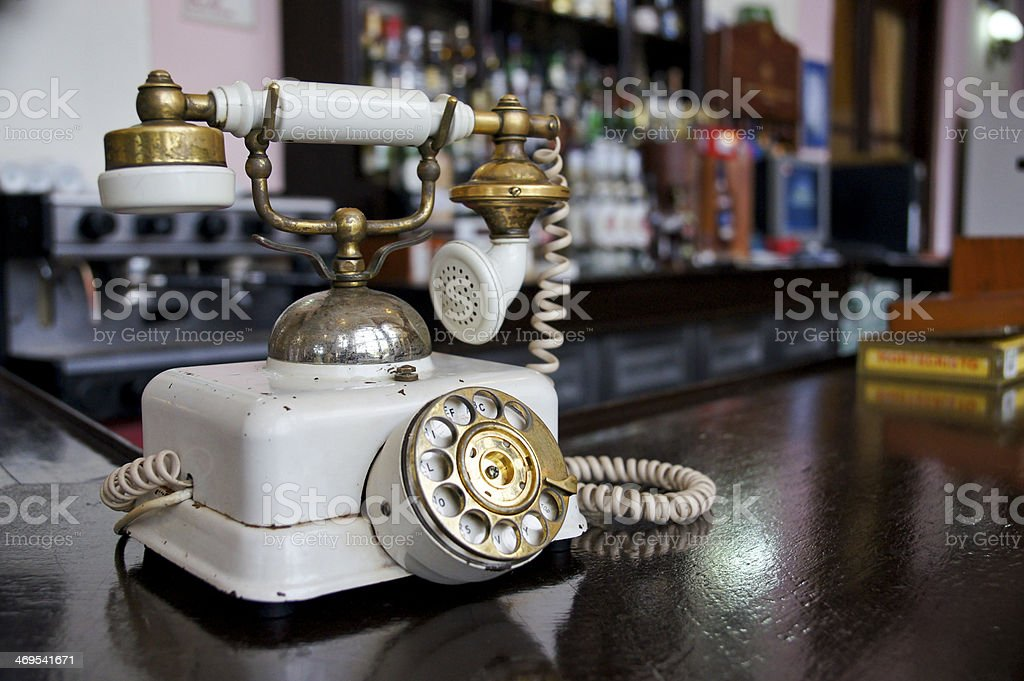 Old fashioned white candlestick phone on wooden desk stock photo