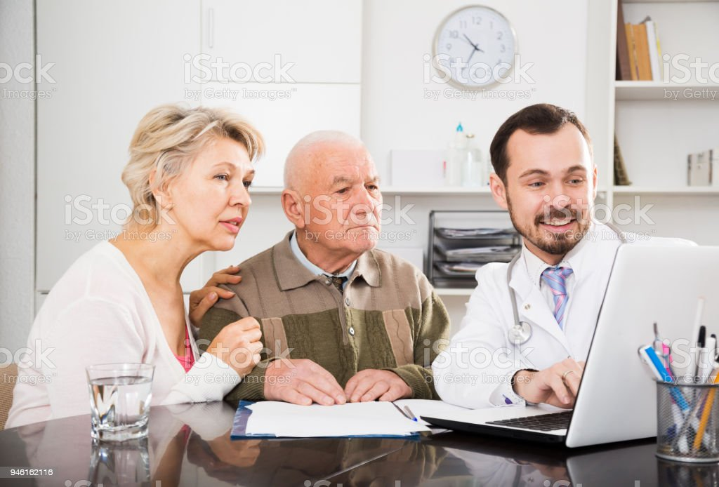 Old father with daughter visit doctor stock photo