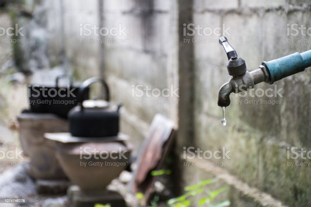 Old faucet and water leaking drop to the ground with blurred...