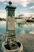 Old faucet in lagoon harbour with ships and green water background