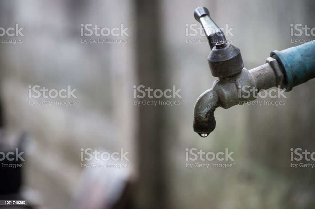 Old faucet with water leaking drop to the ground. Old faucet with water leaking drop to the ground. Accidents and Disasters Stock Photo