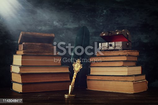 istock Old feather quill ink pen with inkwell and old books over wooden desk in front of black wall background. Conceptual photo on history, fantasy, education and literature topic 1143048417