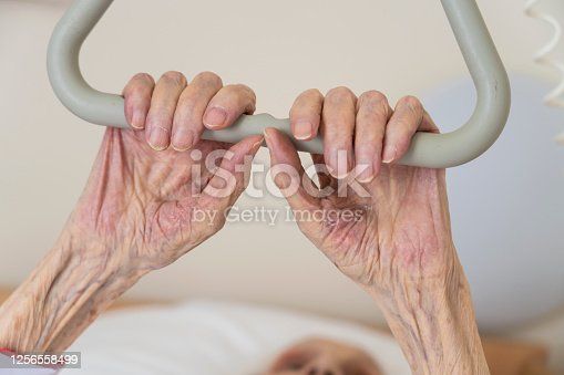 istock Old female hands holding a handle in hospital 1256558499
