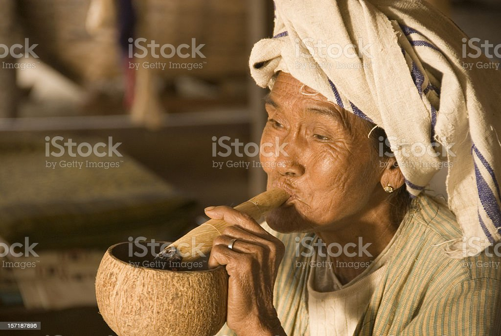 Old female smoking a hand-made cigar royalty-free stock photo