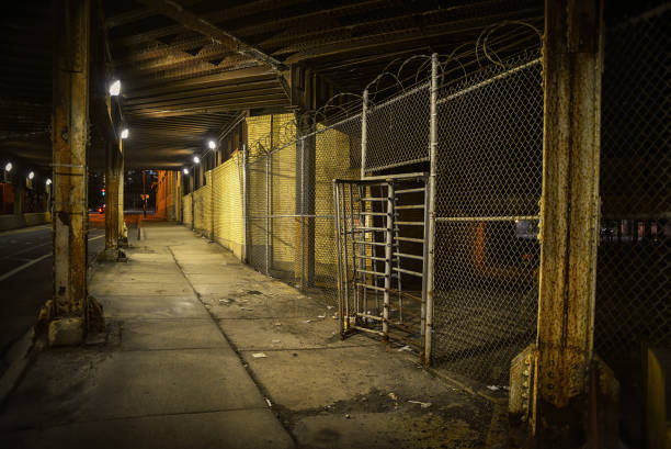 Old fence gate entrance with barbwire under a vintage urban city bridge in Chicago at night stock photo