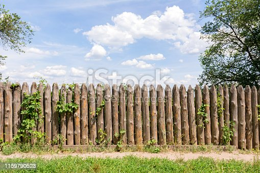 Old fence of logs. Palisade against the blue sky.