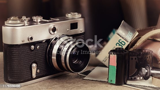 609706398 istock photo Old film camera on wooden table. 1176336495