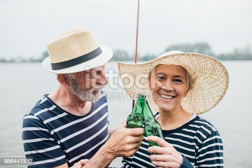 483319252 istock photo Old fisherman drinking beer at the shore with his wife 956441330