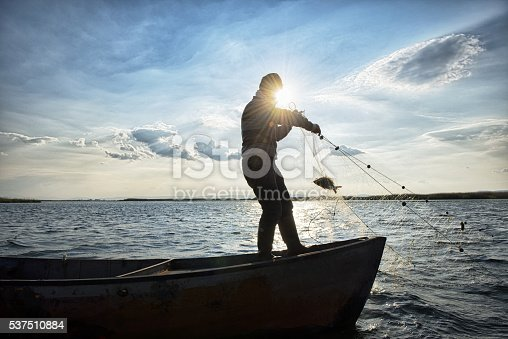 Old fisherman is catching fish with fishing net on his boat, Çivril, Denizli, Turkey.