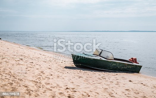 Solitary rest on a deserted river bank. Fishing boat on the background of river landscape