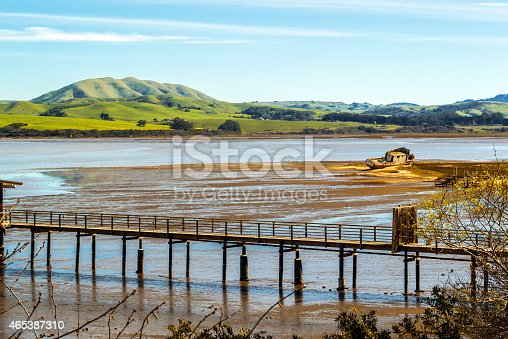 view of old Point Reyes fishing boat in the distance that swept ashore along Tomales Bay in the town of Inverness in Northern California