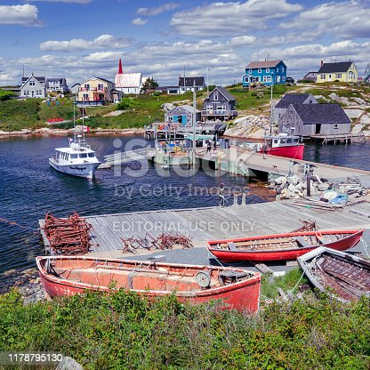 Peggy's Cove, Nova Scotia, Canada - July 10, 2019 -  Old and well used fishing boats lay in disrepair near the wharf. People walk on the wharf sightseeing. The rugged beauty of Peggy's Cove is one of Nova Scotia's major tourist attractions.