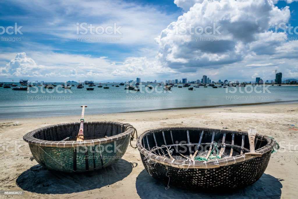 Old fishing boats next to modern sky line in Da Nang stock photo