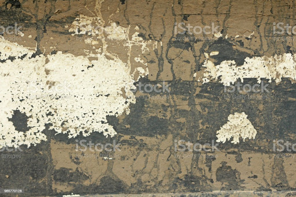 Old Flaky Paint Peeling off a Grungy Cracked Wall. Cracks Old Paint and Plaster on Background of Old Cement Wall. White, Gray and Beige Spots of Paint. An Old Cement Stone Wall as Vintage Cracked - Royalty-free Abstract Stock Photo