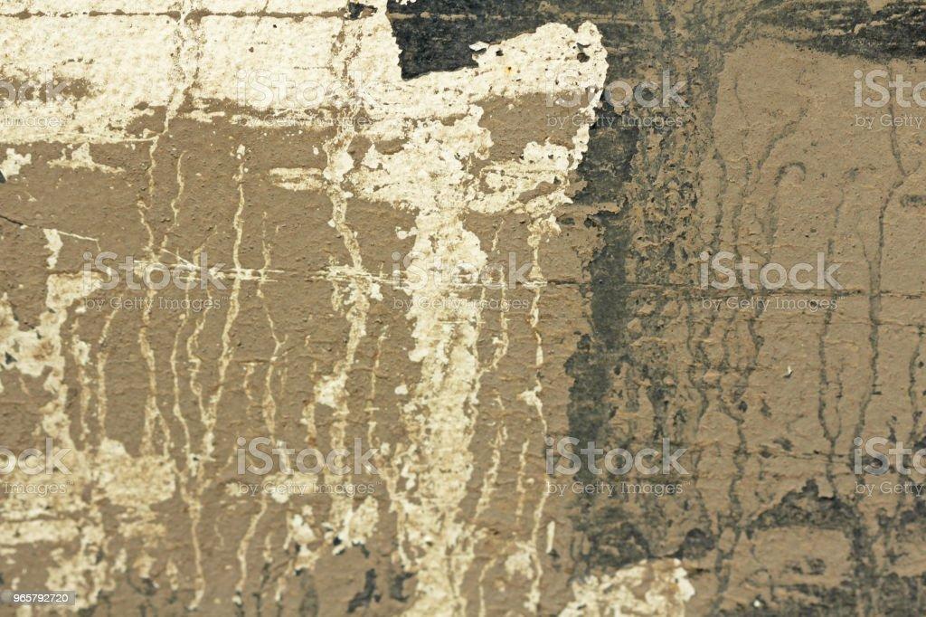Oude schilferige verf Peeling uit een Grungy gebarsten muur. Scheuren van de oude verf en gips op achtergrond van oude Cement muur. Wit, grijs en Beige vlekken van verf. Een oude stenen muur van de Cement als Vintage gekraakt - Royalty-free Abstract Stockfoto