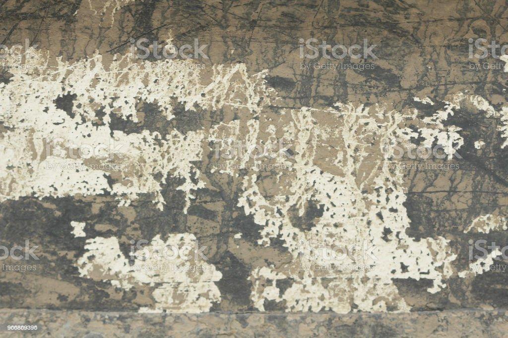 Oude schilferige verf peeling uit een grungy gebarsten muur scheuren