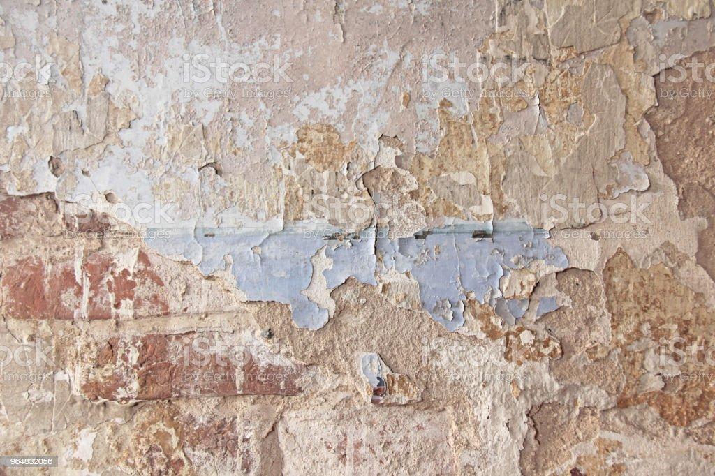 Old flaky white paint peeling off a grungy cracked wall. Cracks, scrapes, peeling old paint and plaster on background of old cement wall. An old cement stone wall as vintage cracked. Brick wall. royalty-free stock photo
