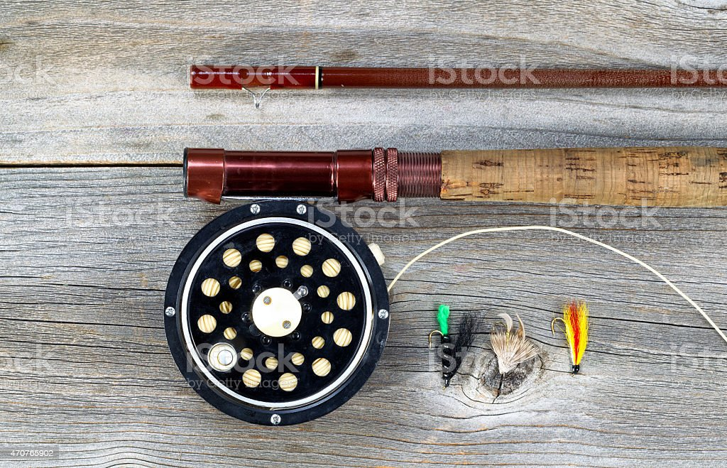 Old fly reel and rod on rustic wood stock photo