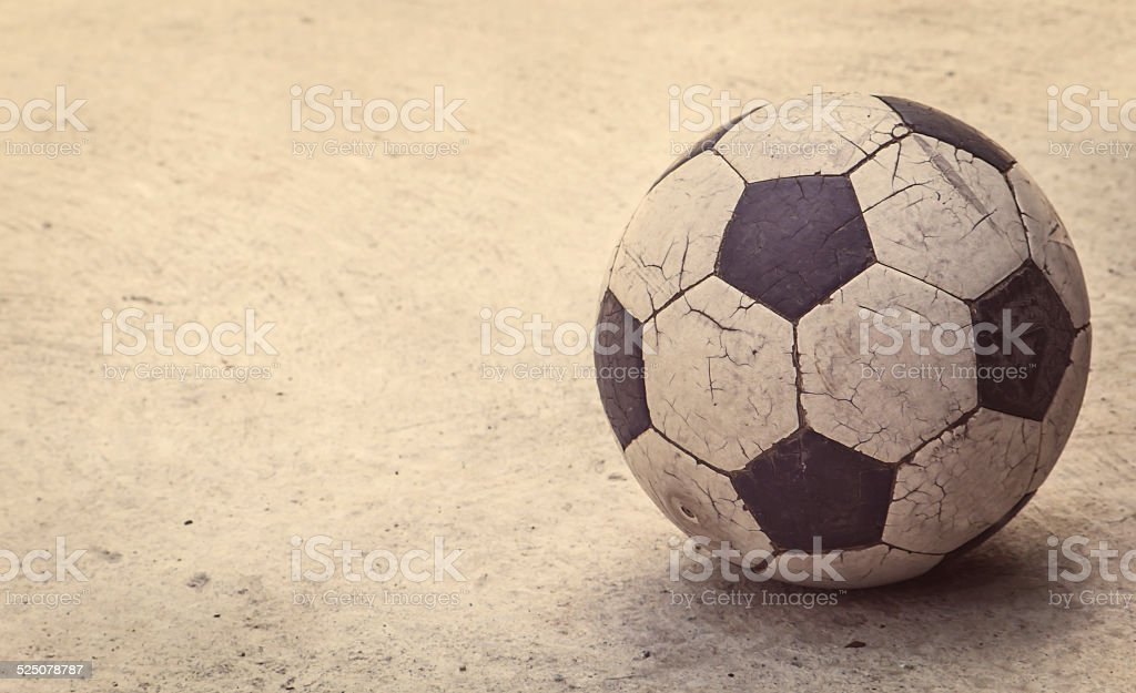 Old football on concrete background, stock photo