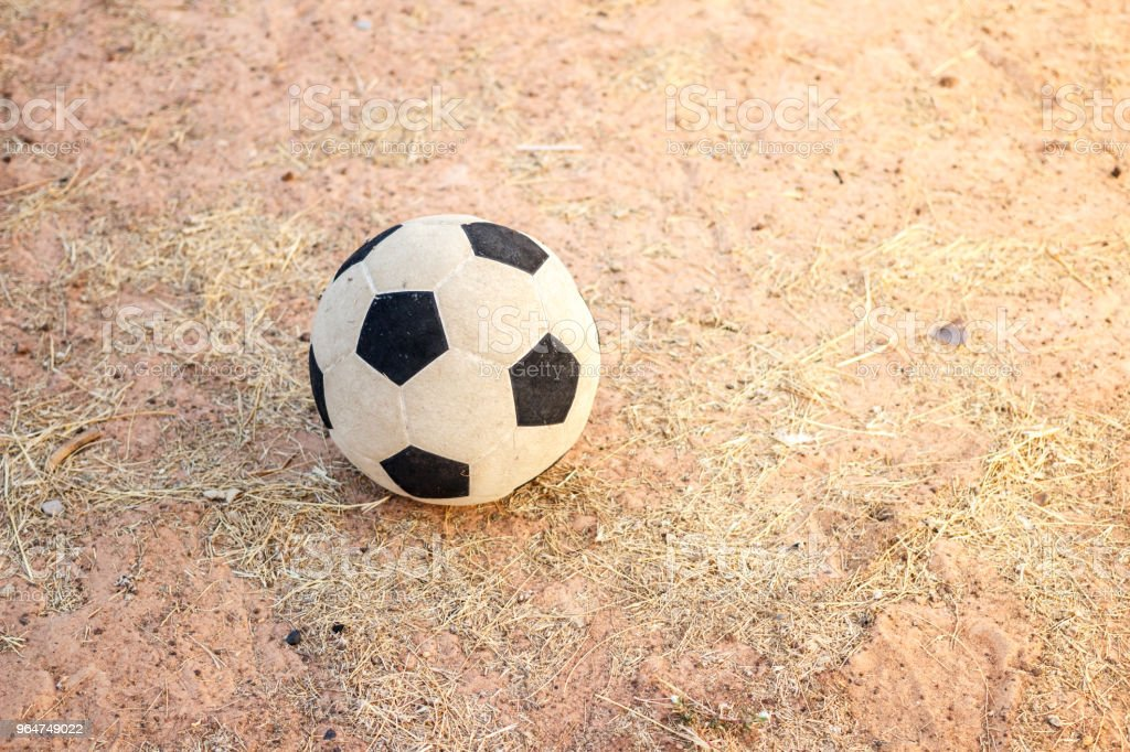 Old football on the dry grass in evening royalty-free stock photo