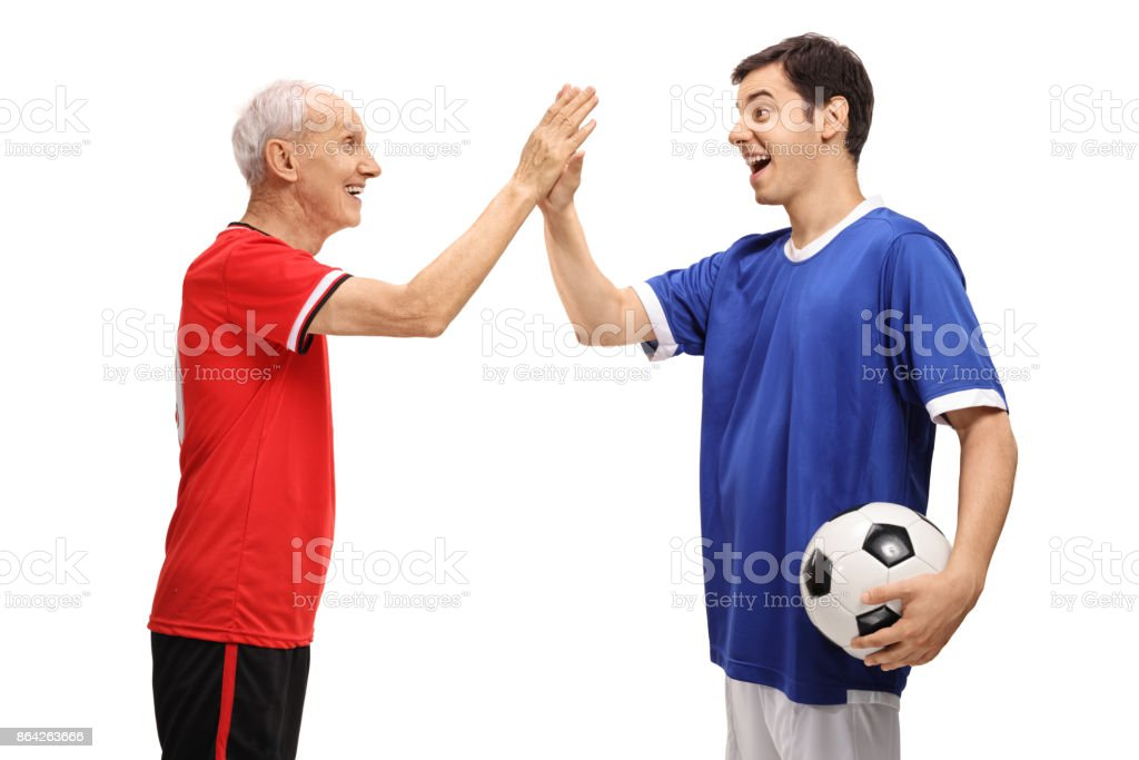 Old footballer and a young footballer high fiving royalty-free stock photo