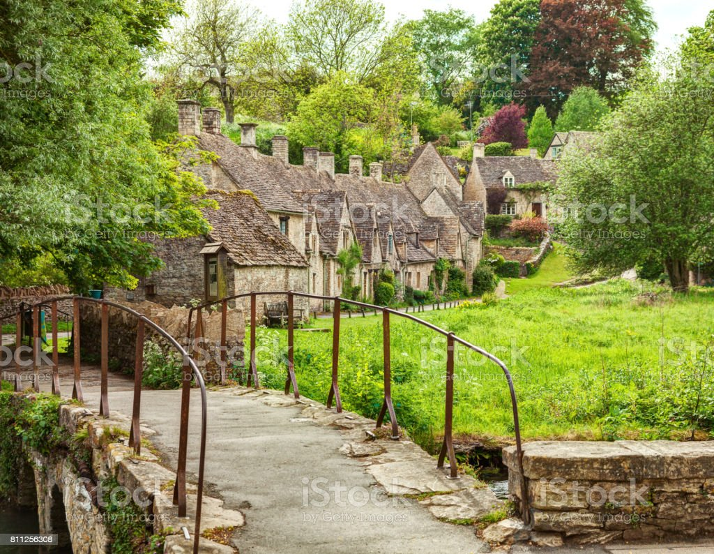 Old footbridge and  traditional Cotswold cottages,   Bibury,  England, UK. stock photo