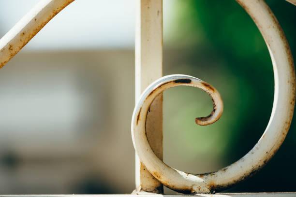 vieille clôture à motifs forgé avec l'écaillage de la peinture blanche, couverte de rouille en plein soleil se bouchent avec espace de copie. fond chaud de fragment de clôture en fer en macro. - motif ornemental photos et images de collection