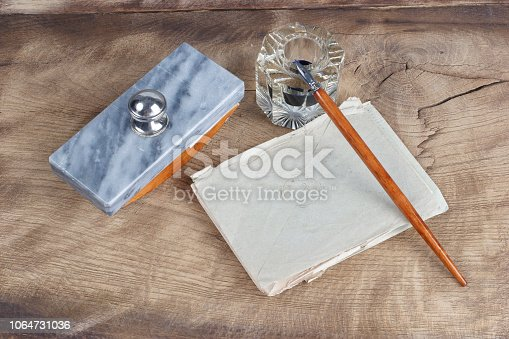 179239584 istock photo Old fountain pen and inkwell with old letters on a wooden background 1064731036