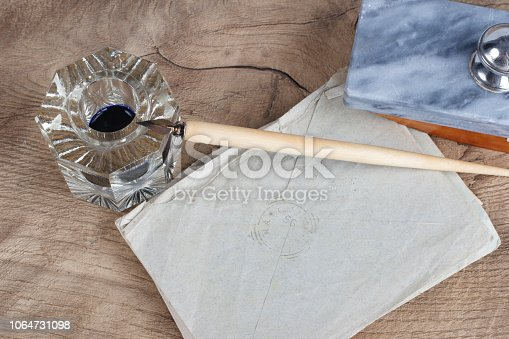 179239584 istock photo Old fountain pen and inkwell with old letters on a wooden background 1064731098