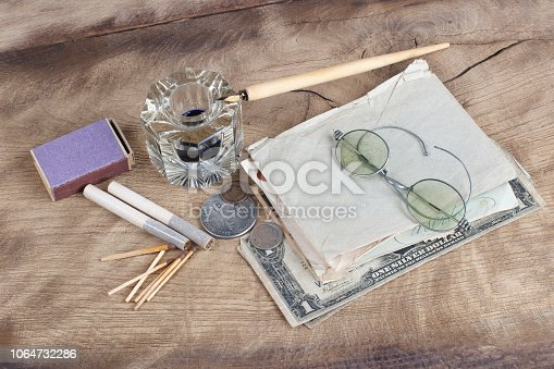179239584 istock photo Old fountain pen and inkwell with old letters on a wooden background 1064732286