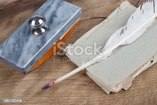 179239584 istock photo Old fountain pen and inkwell with old letters on a wooden background 1064732428