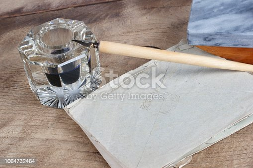 179239584 istock photo Old fountain pen and inkwell with old letters on a wooden background 1064732464