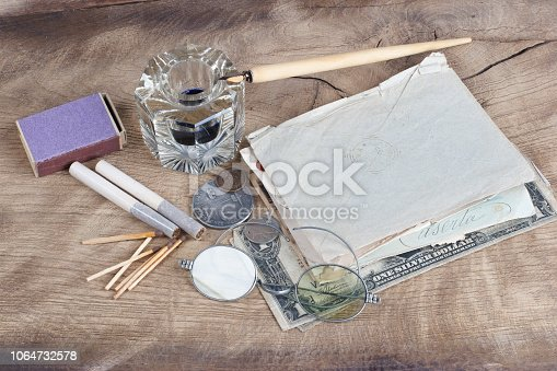 179239584 istock photo Old fountain pen and inkwell with old letters on a wooden background 1064732578