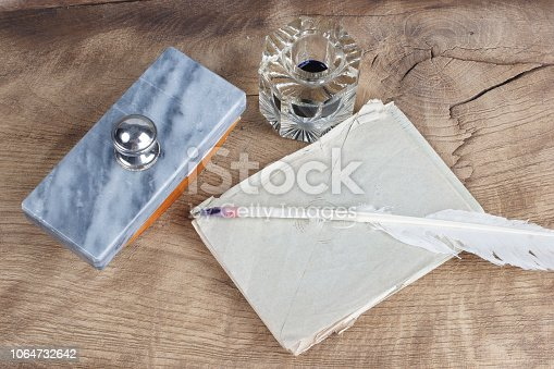 179239584 istock photo Old fountain pen and inkwell with old letters on a wooden background 1064732642