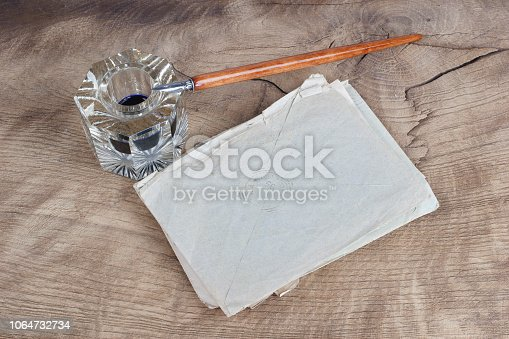 179239584 istock photo Old fountain pen and inkwell with old letters on a wooden background 1064732734